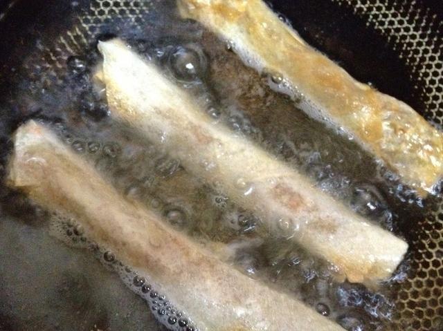 rollos de aceite térmico y primavera fríen hasta que estén doradas. drenar el exceso de aceite en una toalla de papel