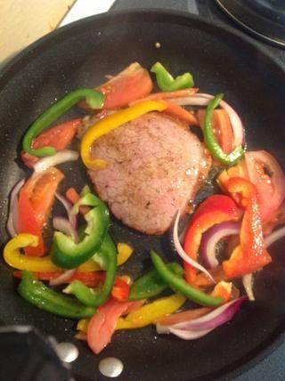 Añadir la carne en la sartén. Voltear cuando se dore un lado. Añadir las verduras.