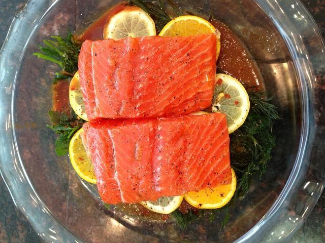 Coloque el salmón encima de una cama de eneldo, albahaca y limón en rodajas. Top con sal, pimienta, y pimentón.