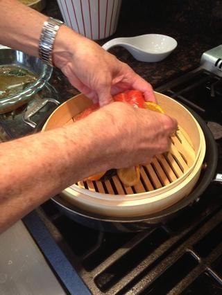 Rellene sartén con agua y colocar vapor japonés en la parte superior. Coloque el salmón encima de vapor, con los limones y las hierbas. Vapor durante unos 10 minutos (dependiendo del grosor) hasta que el salmón es sensible al tacto.