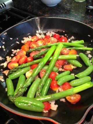Añadir los guisantes dulces, tomates, espárragos y saltee durante aproximadamente 1 minuto para calentar a través. Sazonar con sal, pimienta y un chorrito de aceite de oliva virgen extra y vinagre de champagne.