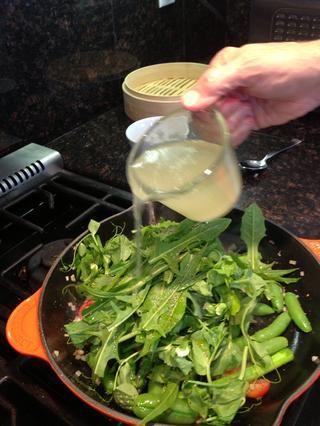 Añadir brotes de guisantes y hojas de diente de león. Vierta un poco de agua de la pasta sobrante (aproximadamente 1/4 taza).