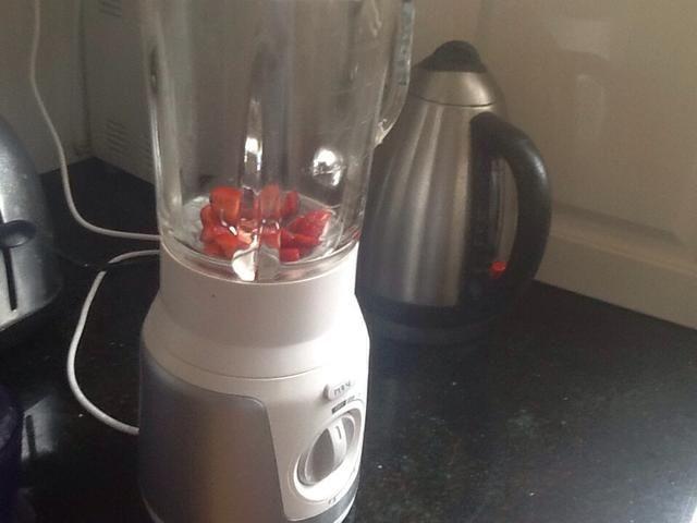 Cortar 4-5 fresas grandes y ponerlos en una licuadora de alimentos