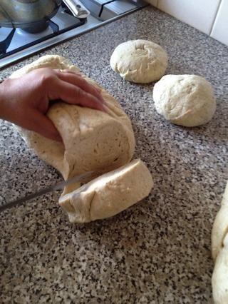 Una vez rised, cortar la masa en 9 partes iguales. Rollo de las piezas en bolas redondas