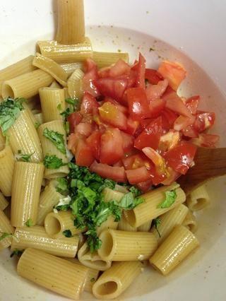 Añadir la pasta al bol, mezclar, agregar los tomates, albahaca y cebolla verde, mezclar.