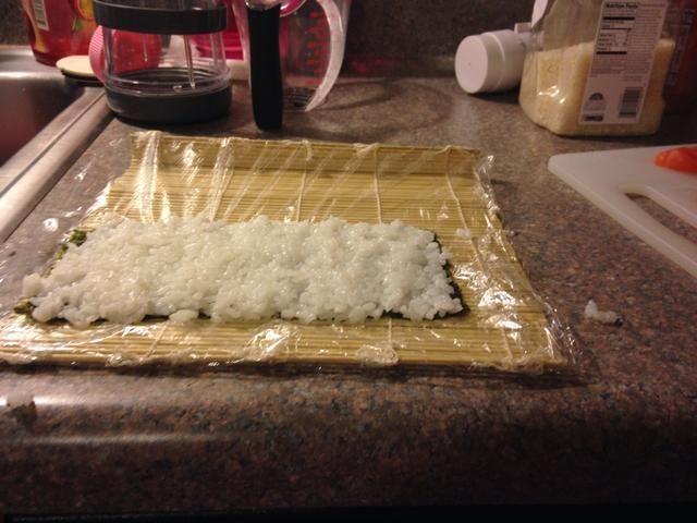 Humedecer las manos y coloque un puñado de arroz pegajoso en el centro del nori y se extendió uniformemente hasta que es aproximadamente 1 cm de espesor