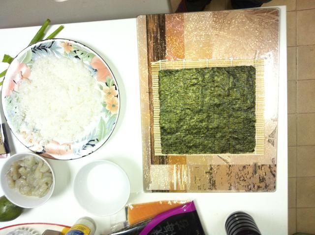 Lugar yaki nori en la estera de sushi con la SIDE NO BRILLANTE (lado arroz) hacia arriba. Obtener el arroz (ahora a temperatura ambiente) y un recipiente con agua limpia listo.