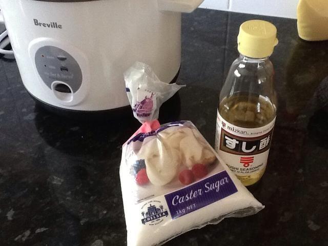 Mida el vinagre azúcar y arroz lanzador y añadir al arroz cocido. Aquí se puede disolver el azúcar en el vinagre pero yo sólo agregarlo al arroz caliente y funciona bien.