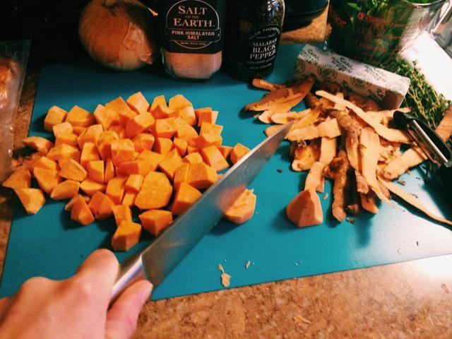 Mientras que el agua comienza a hervir a fuego lento y la mantequilla se derrita, pelar y cortar las patatas dulces en trozos pequeños