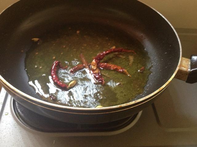 Ponga las especias y chiles secos en el aceite anterior sobre fuego medio-bajo. (En lugar de guindilla seca se puede utilizar fresco pero don't add them now)
