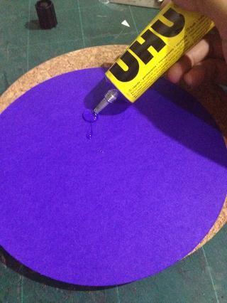 Tome la ronda más grande y colocar sobre el tablero de corcho con pegamento.