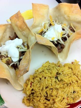 Llenar platos con carne molida, más queso, crema agria y cualquier otro relleno que'd like and pair with Spanish rice.