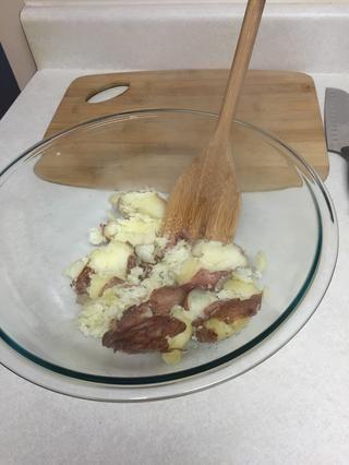 Triturar las patatas en un tazón grande para mezclar.