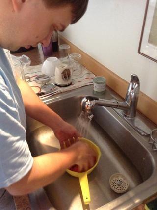 Lavar los tomates ciruela en el fregadero