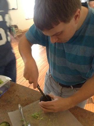 Con cuidado, utilizando la tabla de cortar y un cuchillo cortar el aguacate por la mitad