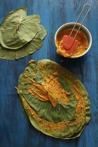 Coloque una hoja de taro (vena hacia arriba) sobre una tabla de cortar y manchar la pasta de harina generosamente. Coloque otra hoja encima y extender la pasta de nuevo. Repetir el proceso para formar una pila de 5 hojas.