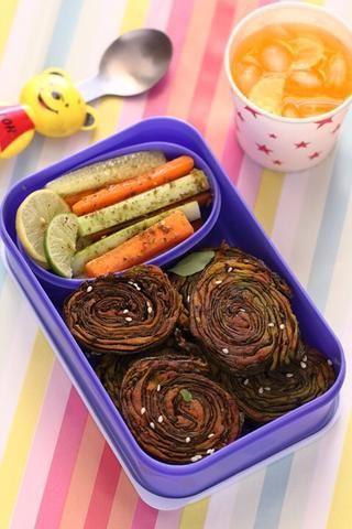 Empaque en lonchera con algunos palitos de verduras y rodajas de limón.