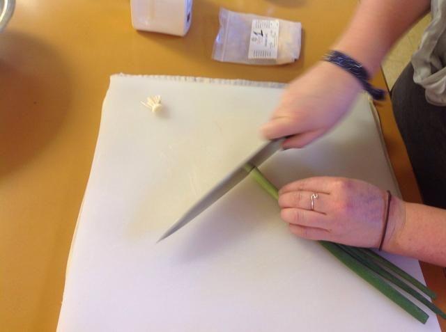 Retire el extremo del tallo de la cebolla de verdeo y comenzar rebanar.