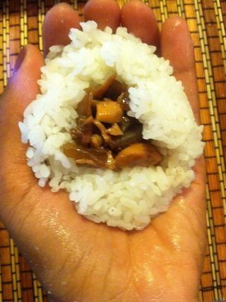 Espolvorear agua y una pizca de sal en las manos, recoger un puñado de arroz y formar un cráter en el medio, a continuación, coloque sus rellenos de salmón en el interior.