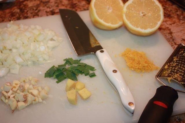 Aproximadamente picar la cebolla, el ajo, hierba de limón, hojas del cafre, y galanga. Si usted no tiene kafir hojas puede ser sustituido con la ralladura de limón. Además, la galanga se puede subbed con jengibre fresco.