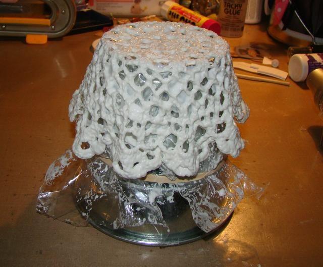 Coloque pañito sobre la lata o recipiente para formar su cesta. Puede crear pliegues en el pañito apretando los lados que le dará un efecto de la colmena en tu cesta. Deje que se seque durante la noche.