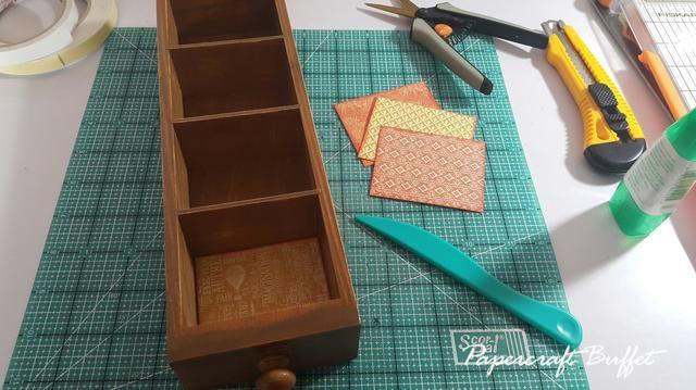 Cortar trozos de papel para cubrir el interior del cajón, aplicar tinta Distress en los bordes le puede dar una buena profundidad.