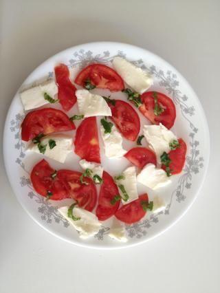 Organizar los tomates y la mozzarella en un plato como este y espolvorear con albahaca fresca.