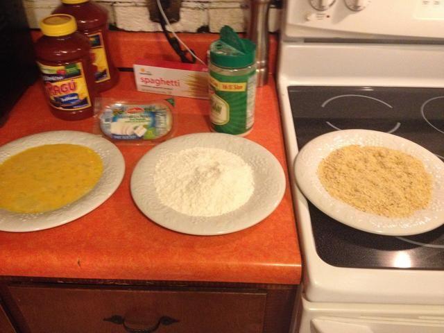Consiga sus platos listos una con huevos crudos revueltos, uno con harina, una con pan rallado