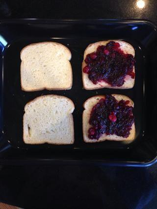 Coloque 4 cucharadas. de salsa de arándanos de dos pedazos de pan.