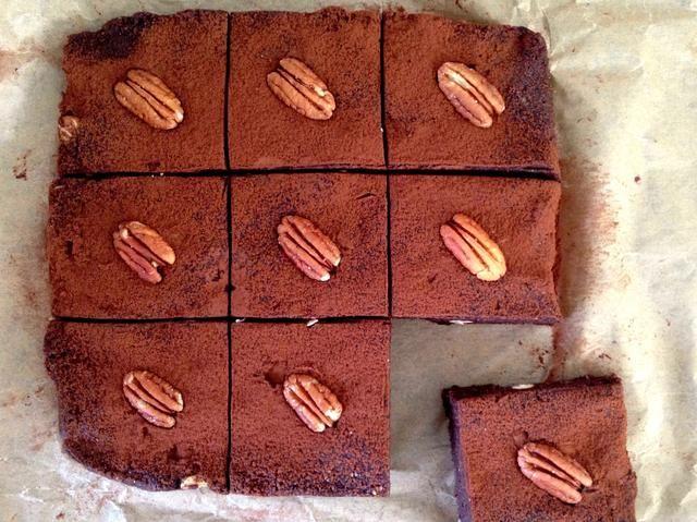 Retire del refrigerador y saque el papel de horno para liberar los brownies. Espolvorear con cacao / cacao y si desea ser súper buches, decorar con nueces o nueces.
