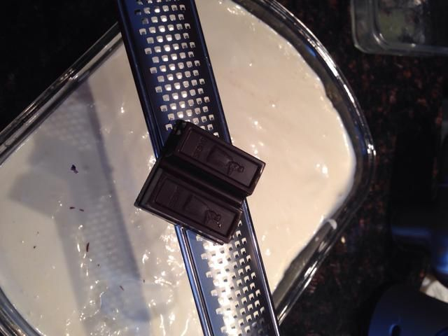 Con un rallador o un rallador, rallar un cuadrado de panaderos de chocolate sobre la capa de queso crema.