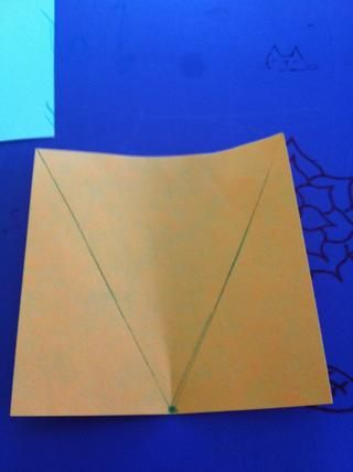 Dibuja 2 líneas desde el punto de las esquinas del papel. Es posible que desee algún tipo de regla.