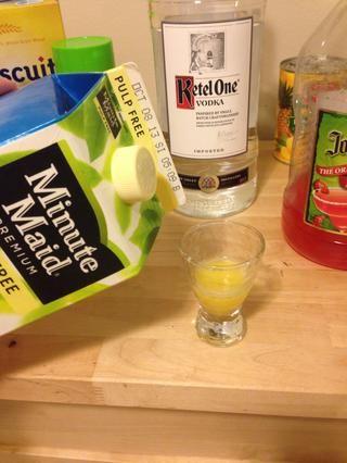 Vierta 1/2 oz de jugo de naranja en un vaso de chupito.