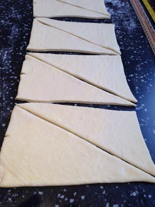 Mida hendiduras 12.5cm a lo largo de la longitud de la masa y cortar en estos puntos para hacer rectángulos. A continuación, corte en diagonal para formar triángulos.