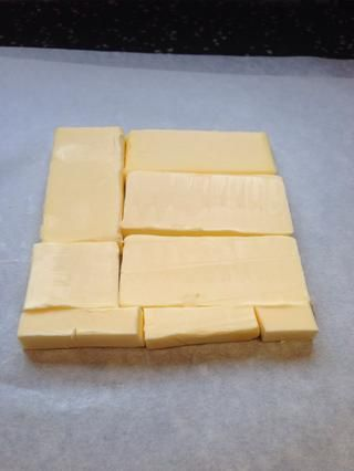 Cortar la mantequilla fría de la nevera lo largo en 1.25cm losas gruesas. Organizar en papel encerado para formar un cuadrado de unos 15x15cm. Cubra con papel encerado y libras con un rodillo hasta que's 19x19 cm