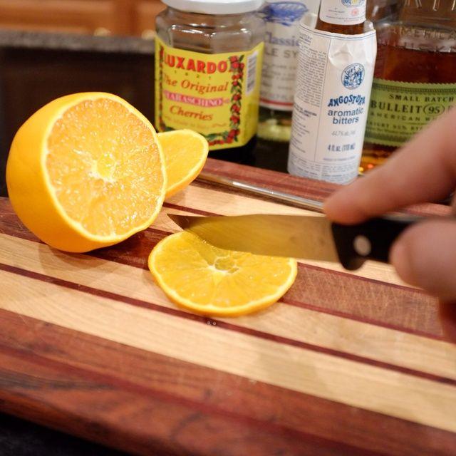 Cortar una sección plana de una naranja, cortar por la mitad y colocarlo en un vaso resistente fondo plano (que segunda rebanada trabajará bien para una segunda copa.)