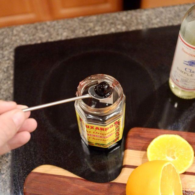 Cuchara de un cereza marrasquino y colocarlo en la rodaja de naranja en el vaso. Personalmente, me gusta Luxardo, pero cualquier haré en un apuro.