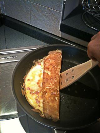 Enrolle la frittata cuando el chese y el jamón son bien cocido pero no quemado