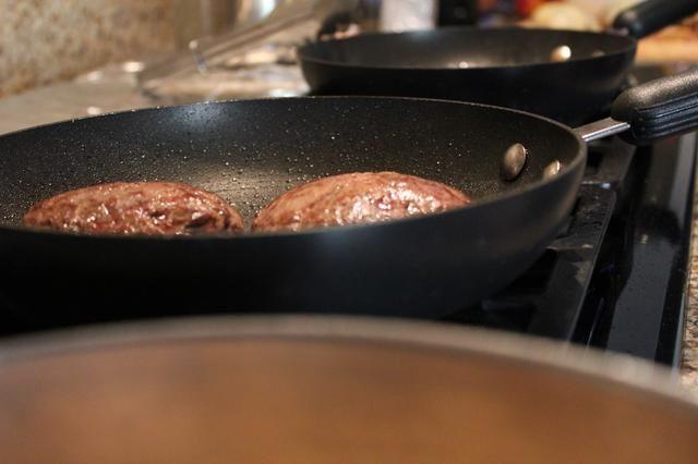 Una vez que la hamburguesa se cocina a su deseo, agregue una rebanada de queso suizo en la cima de la hamburguesa. Cubra la cacerola hasta que el queso se derrita. A continuación, retire las empanadas de la sartén y en una tabla de cortar para descansar.