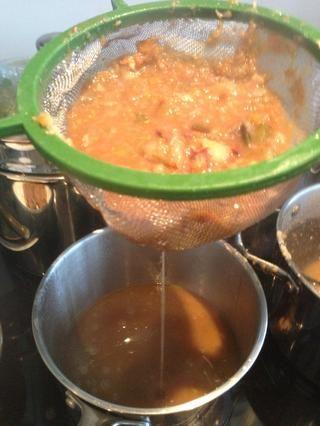 Cocine a fuego lento por 10 minutos y luego reciben un SIV y una segunda bandeja y comienzan a Siv la salsa fuera en la segunda bandeja. Realmente asegúrese de empujar los jugos a través con la cuchara