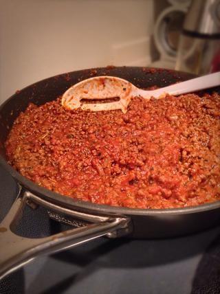 Coloque la carne de nuevo en la sartén, añadir en su salsa para pasta, azúcar, pasta de tomate y sal. Revuelva la mezcla y colocar en un segundo plano a fuego lento durante 30 minutos. Esto permitirá que la mezcla se espese.