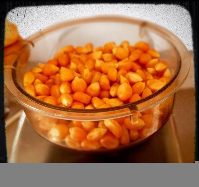 Añadir 1/2 taza de granos de palomitas de maíz para el popper de aire calentado.