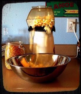 Coloque un recipiente grande en el pico de su máquina de palomitas de maíz.