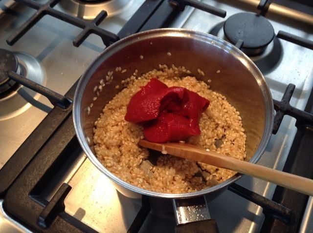 Añadir la pasta de tomate al arroz.