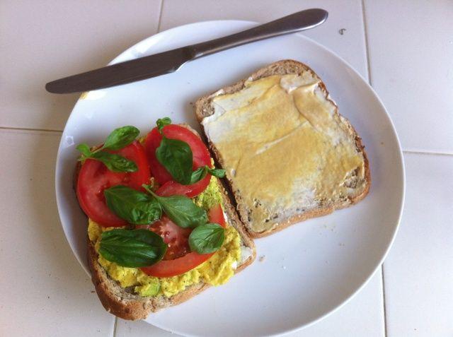 Rebanada de tomate al espesor deseado, añadir a aguacate, luego cubra con sólo unas cuantas hojas de albahaca fresca.