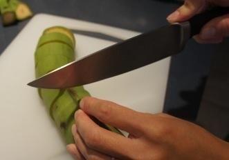 Un método más fácil (creo) es cortar primero el plátano en trozos y luego quitar la piel por cortado longitudinalmente y luego simplemente pelar.
