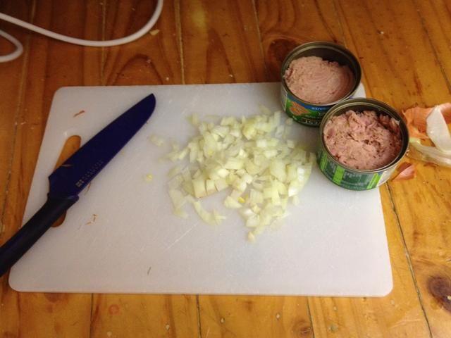 Finamente medio dado una cebolla marrón y drenar las latas de atún.