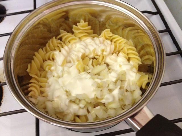 Una vez que la pasta esté cocida, escurrir el agua, a continuación, agregar la crema espesa y la cebolla. Agitar durante un minuto más o menos.