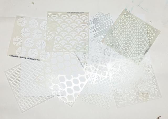 cubrir la cartulina con las plantillas que tienen diseños de estilo más pequeños. puede superponerse y la capa de ellos si lo desea.