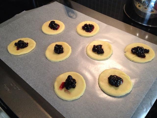 Coloque las galletas en papel de pergamino en una bandeja de horno y cuchara sobre una cucharadita de mermelada en ellos.